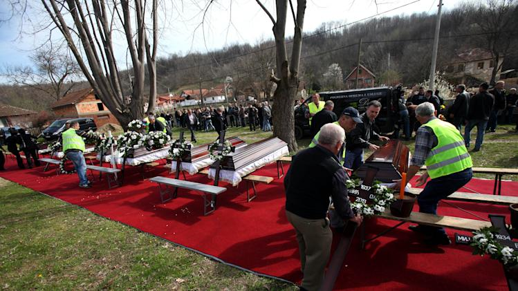 Coffins containing bodies of the victims of a shooting are displayed prior to a mass funeral in the village of Velika Ivanca, some 50 kilometers (30 miles) southeast of Belgrade, Serbia, Friday, April 12, 2013. The village of Velika Ivanca is preparing for the funerals of thirteen victims of a shooting that happened on Tuesday, April 9, 2013. Ljubisa Bogdanovic, a local and a Yugoslav wars veteran, went from house to house on April 9 in the village at dawn, cold-bloodedly gunning down his mother, his son, a 2-year-old cousin and ten other neighbors. (AP Photo/ Darko Vojinovic)