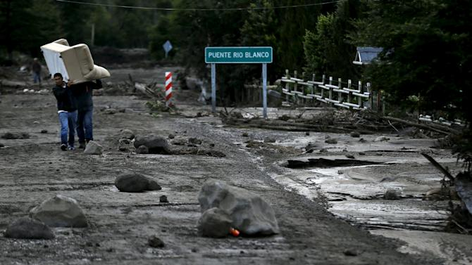 Residents carry a couch through an area damaged by lahar from Calbuco Volcano at Correntoso
