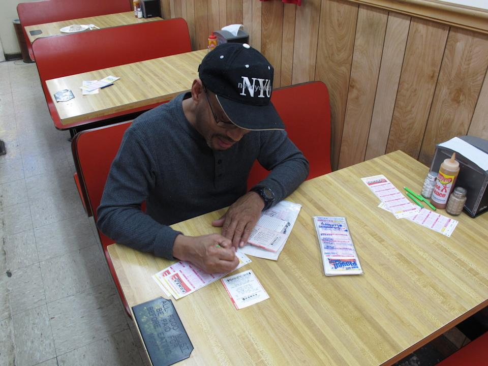 Armous Peterson figures out what numbers he is going to play in the Powerball lottery at Jimmy's Mart on Saturday, May 18, 2013, in Columbia, S.C. Peterson keeps track of what numbers he plays from week to week. (AP Photo/Jeffrey Collins)