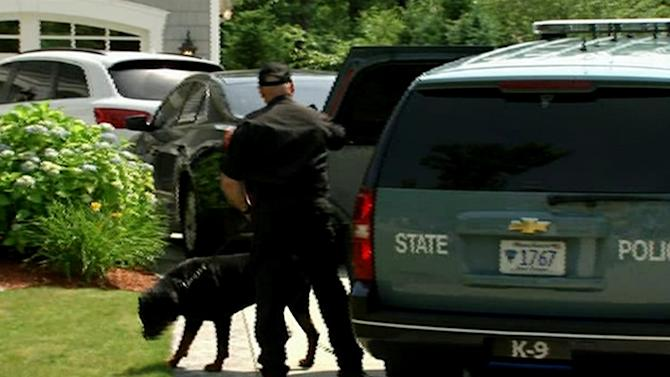 In this image taken from video, a state police officer and dog arrive outside the home of New England Patriots football player Aaron Hernandez, Saturday, June 22, 2013, in North Attleboro, Mass. State police searched Hernandez's home as they investigate the killing of Odin Lloyd, a semi-pro football player whose body was found nearby. (AP Photo/ESPN)