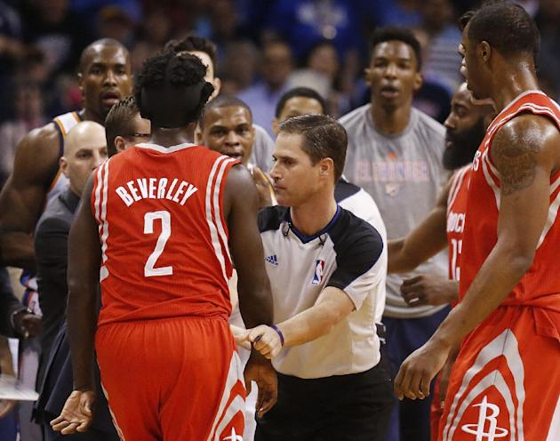 Official David Guthrie, center, holds back Houston Rockets guard Pat Beverley (2) from Oklahoma City Thunder guard Russell Westbrook, between Guthrie and Beverley, during the first quarter of an NBA b