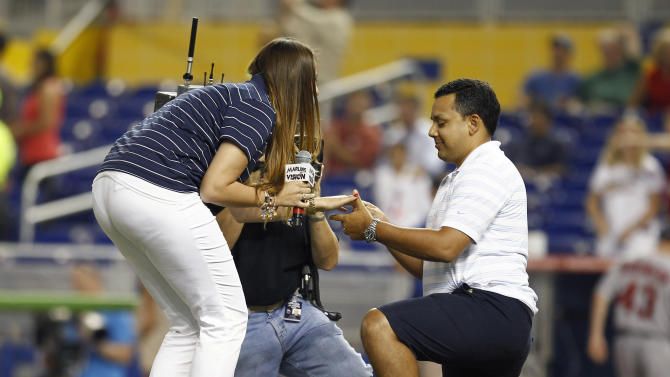 After singing the national anthem, Cassandra Bersach says yes to a surprise marriage proposal from Juan Gallego at Marlins Park before a baseball game between the St. Louis Cardinals and the Miami Marlins on Tuesday, June 26, 2012. (AP Photo/J Pat Carter)