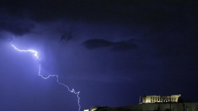 Lightening illuminates the ancient Parthenon temple atop the Acropolis hill in Athens on Sunday Oct. 14, 2012. Greece is inching towards an agreement with its international debt inspectors as they struggle to hammer out the details of euro13.5 billion ($17.5 billion) in austerity measures for the next two years, a package essential for Greece to receive the next installment of its vital bailout funds. (AP Photo/Dimitri Messinis)
