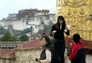 This file photo shows Chinese tourists visiting Jokhang Temple in Lhasa, with a view of the Potala Palace in the background. China&#39;s propaganda chief has ordered officials to intensify the fight against separatism in Tibet, a report said, following a series of self-immolations in protest at Beijing&#39;s rule