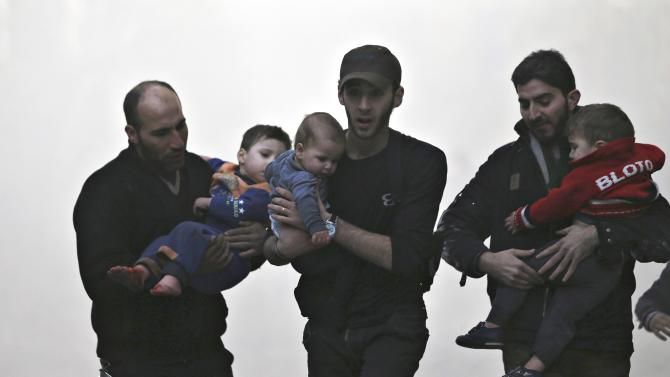 Men rescue children at a site hit by what activists said was an air strike by forces of Syria's President Bashar al-Assad  in the Duma neighbourhood of Damascus