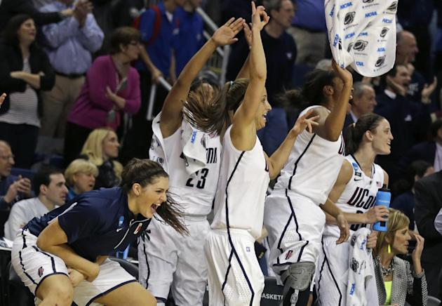 CORRECTS TO STEFANIE DOLSON- Connecticut forward Stefanie Dolson, left, celebrates with her teammates in the final seconds of the second half of a women's NCAA regional final basketball game against K