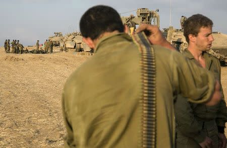 Israeli soldiers gather at a staging area after crossing back into Israel from Gaza