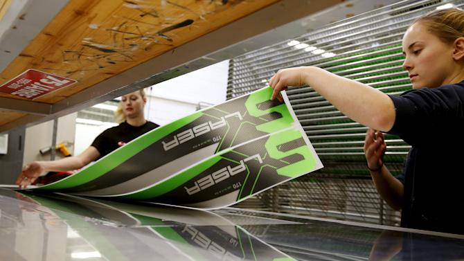 Employees take out the top layer of a ski out of a screen printing machine at the plant of Swiss ski manufacturer Stoeckli in Malters