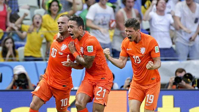 Netherlands' Wesley Sneijder (10) celebrates with teammates Memphis Depay and Klaas-Jan Huntelaar (19) after scoring his side's first goal during the World Cup round of 16 soccer match between the Netherlands and Mexico at the Arena Castelao in Fortaleza, Brazil, Sunday, June 29, 2014