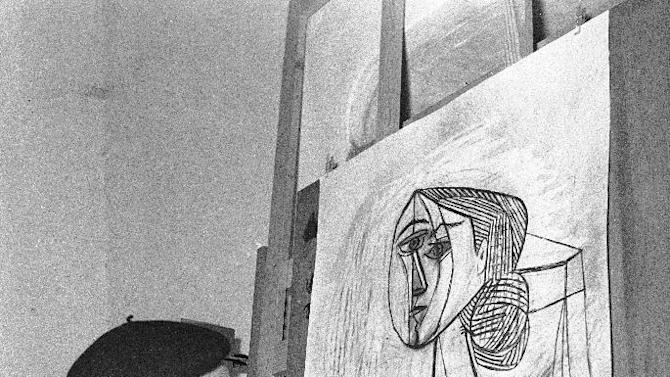 """FILE - In this April 8, 1953 file photo, artist Pablo Picasso looks at a recent painting, """"Portrait of a Woman,"""" in his studio in Vallauris, French Riviera. (AP Photo)"""