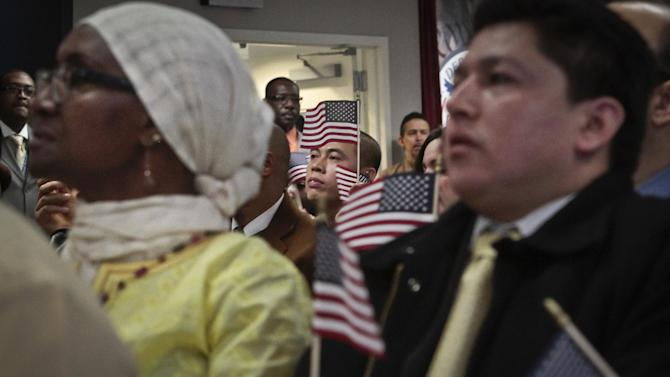 Immigrants hold miniature U.S. flags as they listen to a video broadcast from President Barack Obama during a naturalization ceremony attended by Mayor Michael Bloomberg on Wednesday, Dec. 18, 2013 in New York. A new study finds that Hispanics and Asian-Americans say getting relief from deportations is more important for many of the 11 million immigrants here illegally than creating a pathway to U.S. citizenship. (AP Photo/Bebeto Matthews)