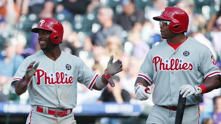Philadelphia Phillies' Jimmy Rollins, left, applauds after scoring on a double by Ryan Howard as teammate Marlon Byrd heads to the plate to bat against the Colorado Rockies in the seventh inning of the Phillies' 10-9 victory in a baseball game in Denver on Sunday, April 20, 2014. (AP Photo/David Zalubowski)