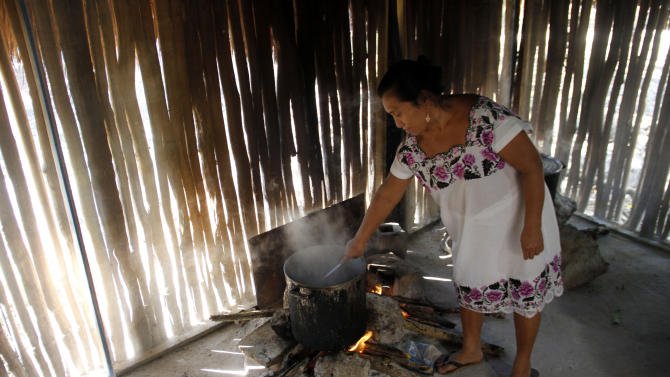 Donaciana Cupul cooks in her home, a traditional stucture, in the Mayan community of Hidalgo in Yucatan state, Mexico Friday, Dec. 14, 2012.  Mexico's 800,000 Mayas are not the sinister, secretive, apocalypse-obsessed race they've been made out to be.  In their heartland on Mexico's Yucatan peninsula, Mayas continue their daily lives. Many still live simply in thatched, oval, mud-and-stick houses designed mostly for natural air-conditioning against the oppressive heat of the Yucatan, where they plant corn, harvest oranges and raise pigs. (AP Photo/Israel Leal)