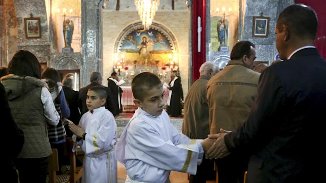 In this Wednesday, Dec. 24, 2014 photo, altar boys shake hands with worshippers as Iraqi Christians celebrate Christmas Eve mass in the Chaldean Church of the Virgin Mary in al-Qoush, northern Iraq, just 12 kilometers (7.5 miles) from the frontline, where Kurdish Peshmerga fighters battle the forces of the Islamic State group. Many of the worshippers are displaced from their homes after Islamic State militants swept through northern Iraq in August. (AP Photo)