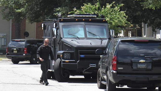 A police officer walks by an armored truck during a search of an apartment complex on Sunday, Aug. 2, 2015, in Memphis, Tenn. Police were looking for a suspect in the fatal shooting of Memphis officer Sean Bolton, who was fatally shot Saturday night. (AP Photo/Adrian Sainz)