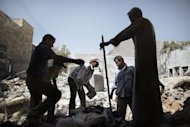 Syrian men sift through the rubble of houses following an air raid by regime forces in Al-Bab, 35 kms (20 miles) northeast of Syria's commercial capital Aleppo