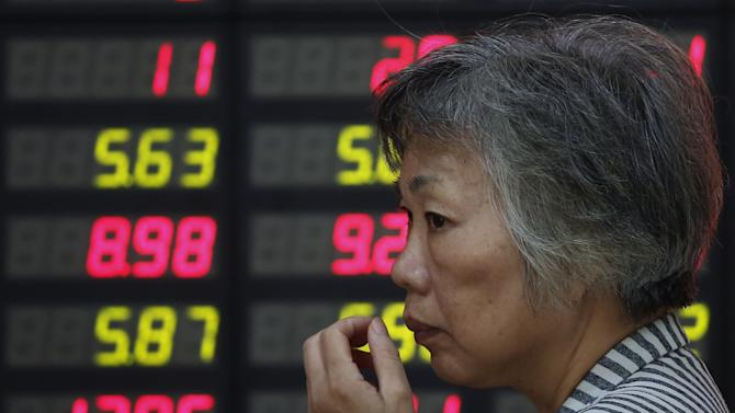 An investor looks at the stock price monitor at a private securities company Friday Sept. 21, 2012 in Shanghai, China. China's benchmark Shanghai Composite Index added 0.1 percent to 2,027.03 Friday, as Asian stock markets rebounded, led by oil and technology shares, despite uncertainty about the fragile global economy. (AP Photo)