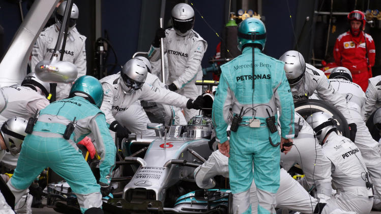 Mercedes driver Nico Rosberg of Germany is surrounded by his pit crew during a pit-stop in the Australian Formula One Grand Prix at the Albert Park in Melbourne, Australia, Sunday, March 16, 2014. Rosberg won the race. (AP Photo/David Gray, Pool)