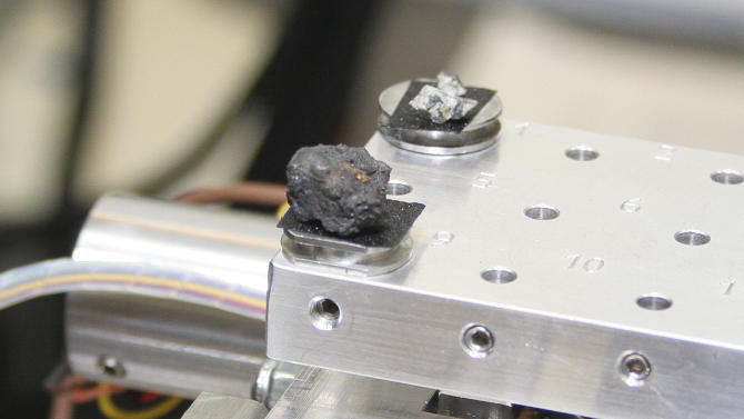 In this photo distributed by the Urals Federal University Press Service pieces of a meteorite are seen in a laboratory in Yekaterinburg on Monday, Feb.18, 2013. Researchers from the Urals Federal University, based in Yekaterinburg, have determined that the small stone-like pieces found near Lake Cherbarkul in the Chelyabinsk region are pieces of the meteorite that exploded over the region Feb. 15. A total of 53 pieces have been brought for analysis to the university in Yekaterinburg. The largest one is one centimeter in diameter, the smallest is about one millimeter. It is written in Cyrillic: Meteorite Chebarkul. (AP Photo/ The Urals Federal University Press Service, Alexander Khlopotov)