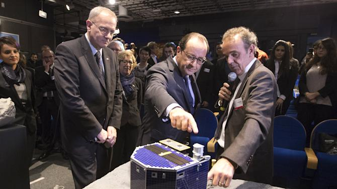 File photo of CNES president Le Gall, French President Hollande and astrophysicist Rocard inspecting a scale model of Rosetta lander Philae in Paris