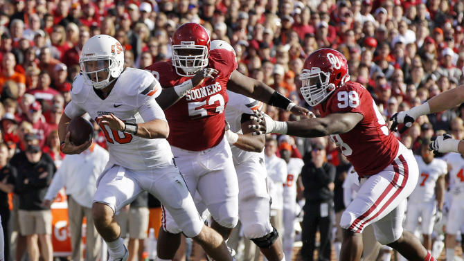 Oklahoma State quarterback Clint Chelf (10) carries in front of Oklahoma defensive tackle Casey Walker (53) and defensive end Chuka Ndulue (98) in the first quarter of an NCAA college football game in Norman, Okla., Saturday, Nov. 24, 2012. (AP Photo/Sue Ogrocki)
