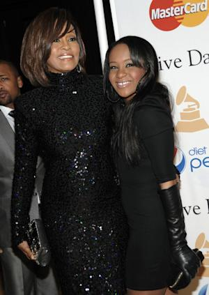 """FILE - In this Feb. 12, 2011 file photo, singer Whitney Houston, left, and her daughter Bobbi Kristina arrive at the Pre-Grammy Gala & Salute to Industry Icons with Clive Davis honoring David Geffen in Beverly Hills, Calif. A reality show featuring Whitney Houston's relatives, including daughter Bobbi Kristina and mother Cissy, is in the works. Houston rep Kristen Foster confirmed the Lifetime show """"The Houston Family Chronicles"""" on Friday, May 11, 2012. Houston drowned in a bathtub in February at age 48, a death that was complicated by cocaine use. (AP Photo/Dan Steinberg, file)"""