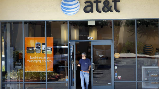 FILE - In this July 22, 2009 file photo, a customer walks out of an AT&T store in San Jose, Calif. AT&T Inc. on Friday July 12, 2013 said that it has agreed to acquire Leap Wireless International Inc., the pre-paid cellphone carrier that operates under the Cricket brand, for about $1.19 billion in cash or $15 a share. (AP Photo/Marcio Jose Sanchez, File)