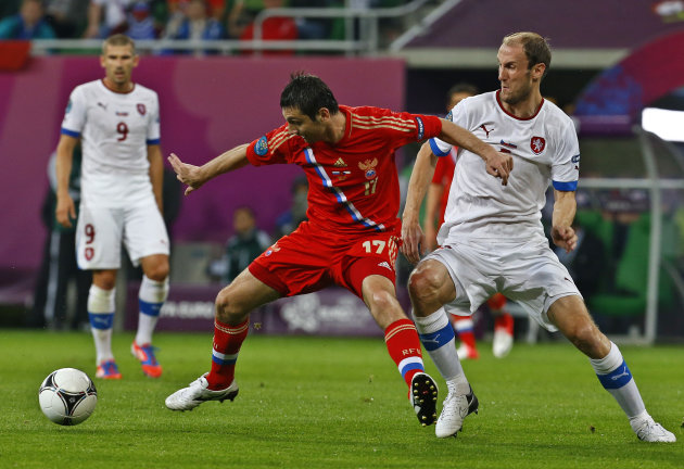 Russia's Alan Dzagoyev and Czech Republic's Roman Hubnik fight for the ball during the Euro 2012 Group A soccer match between Russia and Czech Republic, in Wroclaw, Poland, Friday, June 8, 2012. In the back is Czech Republic's Jan Rezek. (AP Photo/Sergey Ponomarev)