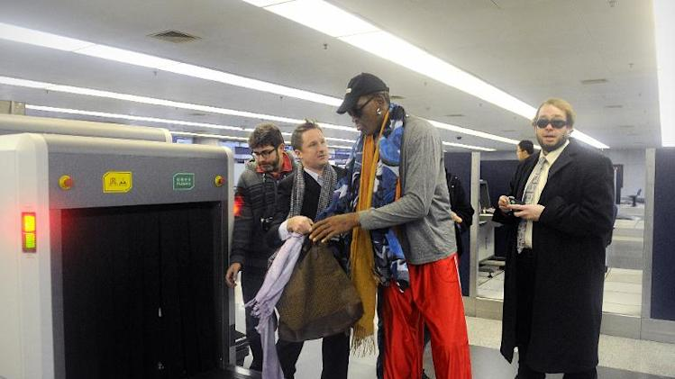 Former NBA basketball player Dennis Rodman goes through a security check at Beijing's international airport on December 19, 2013