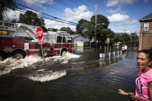 A resident watches as emergency personnel drive their truck through a flooded intersection in Islip, New York
