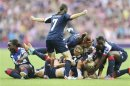 Britain's Houghton celebrates scoring on Brazil with teammates during their women's Group E football match at the London 2012 Olympic Games at Wembley stadium in London