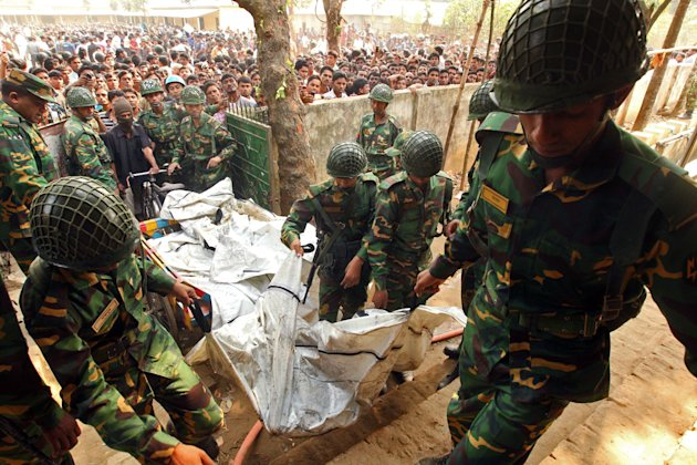 Army soldiers carry the bodies of workers were killed in a fire at a garment factory in the Savar neighborhood in Dhaka, Bangladesh, Sunday Nov. 25, 2012. At least 112 people were killed in a late Sat