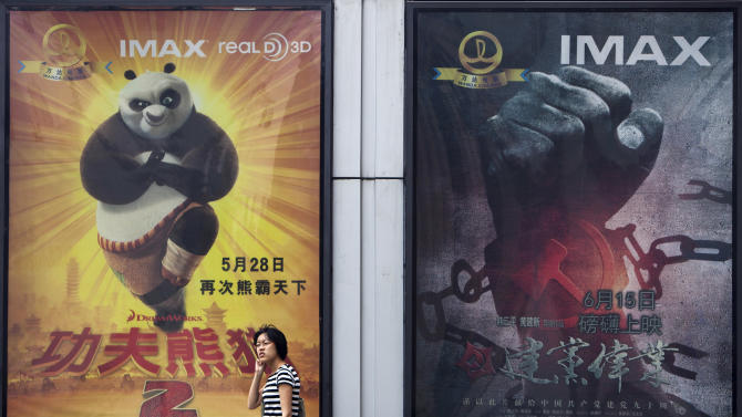 """In this photo taken on June 15, 2011, a woman walks past movie posters of Hollywood movies """"Kung Fu Panda 2,"""" left, and China's propaganda film """"Beginning of the Great Revival"""" on display side by side outside a cinema in Beijing. DreamWorks Animation and Chinese partners announced plans Tuesday, Aug. 7, 2012 to co-produce the next """"Kung Fu Panda"""" movie and develop an entertainment district in Shanghai, expanding Hollywood's fast-growing ties to China. (AP Photo/Andy Wong)"""