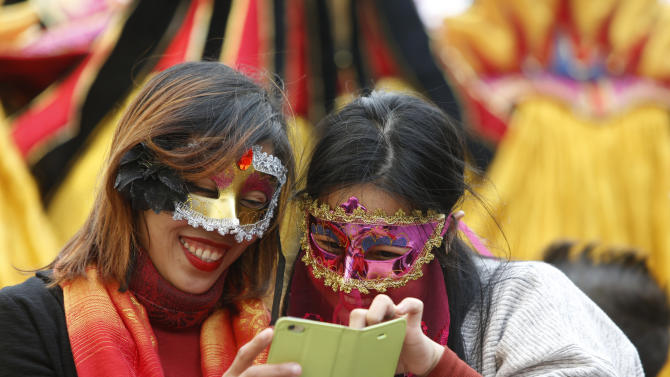 Two masked tourists use a mobile device during carnival celebrations in Valletta