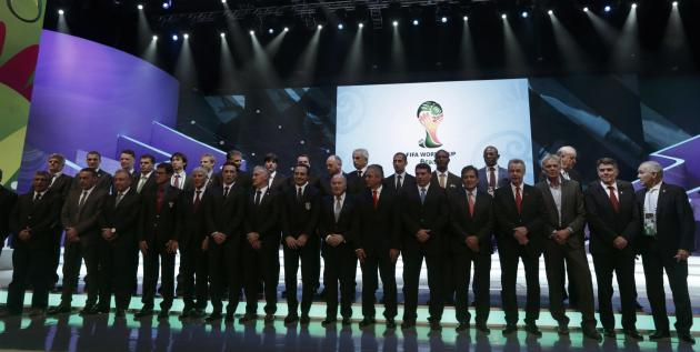 Blatter poses with soccer coaches for a group photo during the draw for the 2014 World Cup in Sao Joao da Mata