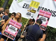 "<p>People hold signs reading ""Enough with savings fraud"" and ""Enough with the abuses of banks"" as they take part in a demonstration against the European Union and Spanish government bailout of Bankia.</p>"