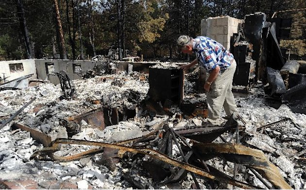 Richard Hoffman walks through the remains of his house in Colorado Springs, Colo., as some residents were allowed to return to their homes Tuesday, June 18, 2013. The Black Forest fire has destroyed 5