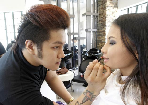 John Claude Ganibe, 21, meticulously applies lipstick to a model while practicing in womenÕs make-up application inside the salon area of the Tony Galvez School of Cosmetology in metro Manila