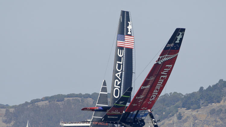 Emirates Team New Zealand, right, nearly capsizes next to Oracle Team USA, left, while heading for the windward marks during the eighth race of the America's Cup sailing event Saturday, Sept. 14, 2013, in San Francisco. Oracle Team USA won the eighth race and the ninth race was called because of high wind Saturday. (AP Photo/Eric Risberg)
