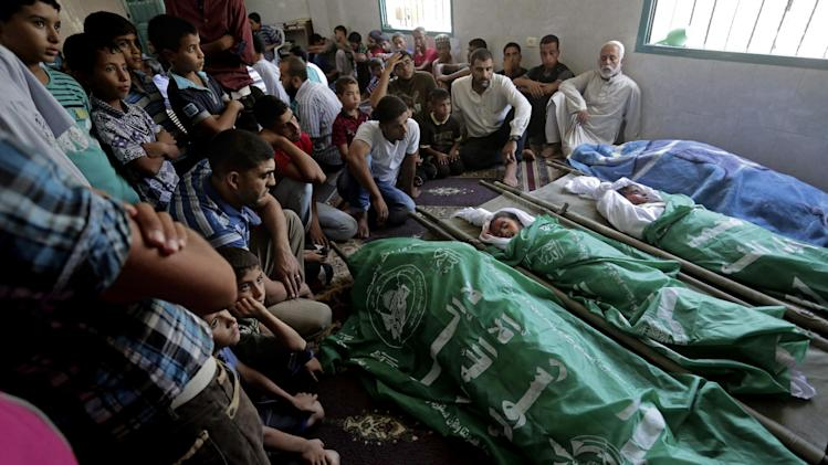 Palestinians mourn during the funeral of members of the al-Louh family who were killed in an Israeli strike on their home in Deir el-Balah, in the central Gaza Strip, Wednesday, Aug. 20, 2014. Many were killed in an airstrike on the house of the al-Louh family in Deir el-Balah, including a mother, father, three children, and two brothers of the father, according to Gaza health official Ashraf al-Kidra. (AP Photo/Adel Hana)