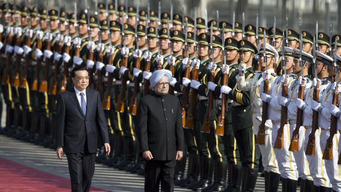 Indian Prime Minister Manmohan Singh, right, is accompanied by Chinese Premier Li Keqiang, left, as they inspect an honor guard during a welcome ceremony outside the Great Hall of the People in Beijing, China Wednesday, Oct. 23, 2013. China and India signed a confidence-building accord Wednesday to cooperate on border defense following a standoff between armed forces of the two Asian giants in disputed Himalayan territory earlier this year. (AP Photo/Andy Wong)