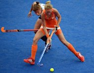 Carlien Dirske Van Den Heuvel (front) of the Netherlands attempts to go past Kim Young Ran of South Korea during the women's field hockey preliminary round match at the Riverbank Arena in London. Defending champions the Netherlands moved into the semi-finals of the Olympic women's hockey tournament on Saturday by defeating South Korea 3-2 for their fourth successive victory in London