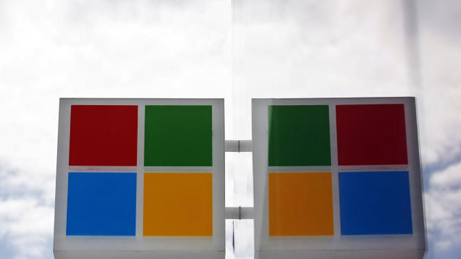 The new Microsoft logo is seen reflected in windows at a company store Thursday, Aug. 23, 2012, in Seattle. Microsoft's new corporate logo sets the stage for a wave of products designed to cast the world's largest software maker in a new light. The makeover unveiled Thursday marks the first time that Microsoft Corp. has revamped its logo since February 1987. The Internet was barely around then, and cellphones were considered a luxury. (AP Photo/Elaine Thompson)