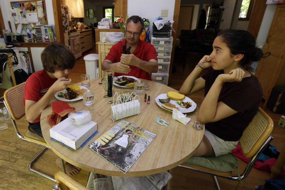 In this Friday, June 14, 2013 photo, Karl Owen has lunch with his children Marcus, left, and Jordan in their Chapel Hill, N.C. home. Owen lost his wife and the mother of their two children to cancer three years ago. (AP Photo/Gerry Broome)
