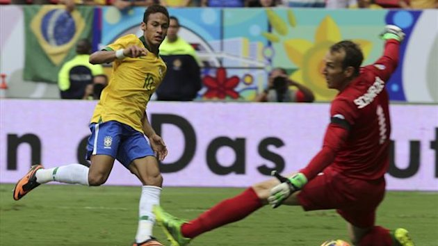 Brazil's Neymar (L) scores a goal against Australia's goalkeeper Mark Schwarzer during their international friendly match in Brasilia September 7, 2013.