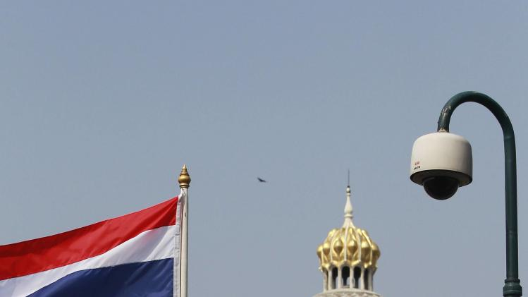An anti-government protester holds a Thai national flag as he climbs onto a fence of the Government House during a rally in Bangkok