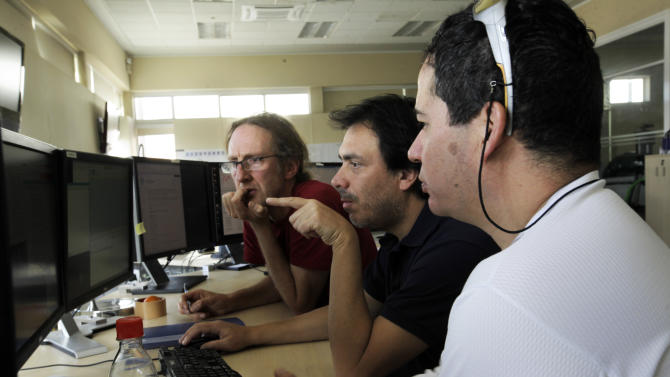 In this Sept. 26, 2012 photo, astronomer Bill Dent, left, engineer Rodrigo Amestica, center, and array operator Patricio Alvarez work at the Operations Support Facility of one of the worlds largest astronomy projects, the Atacama Large Millimeter/submillimeter Array (ALMA) in the Atacama desert in northern Chile. The lack of humidity, low interference from other radio signals and closeness to the upper atmosphere in this remote plateau high above Chile's Atacama desert, is the perfect spot for the ALMA, the earth's largest radio telescope, which is on track to be completed in March. (AP Photo/Jorge Saenz)