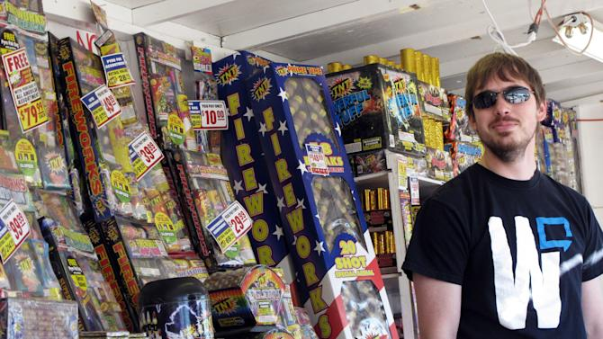 In this Thursday, June 28, 2012 photo, TNT Fireworks employee Casey Hern stands in front of fireworks for sale, in Helena, Mont. Montana officials have urged people not to shoot fireworks while extreme wildfire conditions exist. (AP Photo/Matt Volz)