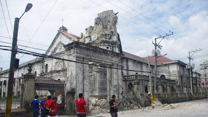 Filipinos stand by a damaged Basilica Del Sto Nino in Cebu, central Philippines Tuesday, Oct. 15, 2013. A 7.2-magnitude earthquake collapsed buildings, cracked roads and toppled the bell tower of the Philippines' oldest church Tuesday morning, killing at least 20 people across the central region. (AP Photo/Chester Baldicantos)