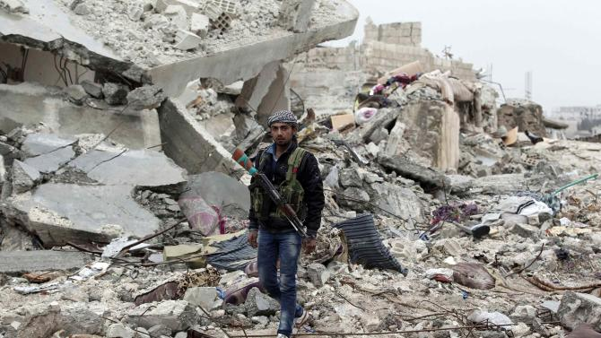 Fighter of the Kurdish People's Protection Units walks on the debris of a destroyed building in the northern Syrian town of Kobani